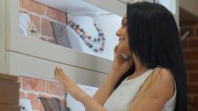 Jeune joli client parlant avec son ami au téléphone et demandant un nouveau nacklace comme cadeau Images stock
