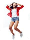 Jeune joli emitonal posant l'adolescente sur le fond rouge lumineux sautant avec des cheveux de vol, mode de vie de sourire heure Photographie stock libre de droits