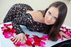 Jeune joli femme avec un véhicule neuf dans le peta rose de rouge Photographie stock