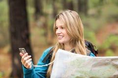 Jeune joli randonneur employant la boussole et la carte image libre de droits