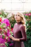 Jeune joli wooman entre les fleurs rouges photo stock