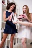 Jeune jolie dame se tenant à une jambe tandis que son ami vérifiant la nouvelle taille de chaussures la comparant à de vieilles c Photos stock