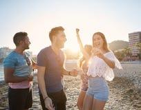 Jeune jolie danse de femme avec des amis sur la plage Image stock