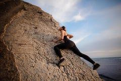Jeune jolie escalade sportive de fille sans carabines et corde, bouldering Photographie stock libre de droits