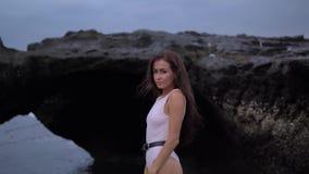 Jeune jolie femelle avec de longs cheveux bouclés foncés dans les promenades blanches de vêtements de bain près de la roche sur l clips vidéos