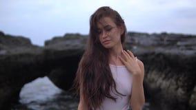 Jeune jolie femelle avec de longs cheveux bouclés foncés dans les supports blancs de vêtements de bain près de la roche noire sur clips vidéos