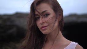 Jeune jolie femelle avec de longs cheveux bouclés foncés dans les supports blancs de vêtements de bain près de la roche sur la pl banque de vidéos