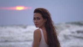 Jeune jolie femelle avec de longs cheveux foncés dans les regards blancs de vêtements de bain dans la caméra sur la plage d'océan banque de vidéos