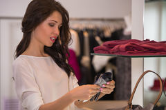 Jeune jolie femme à la boutique de luxe choisissant des accessoires Image stock