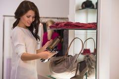 Jeune jolie femme à la boutique de luxe choisissant des accessoires Image libre de droits