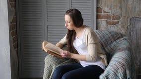 Jeune jolie femme à la maison s'asseyant sur la chaise moderne, livre de lecture banque de vidéos