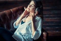 Jeune jolie femme avec des écouteurs Photographie stock