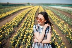 Jeune jolie femme avec des lunettes de soleil dans un jardin avec beaucoup de tulipes jaunes Photo stock