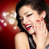 Jeune jolie femme avec la manucure et les languettes rouges Photos stock