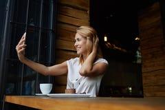 Jeune jolie femme avec le beau sourire posant tout en se photographiant sur l'appareil-photo de téléphone portable, Images stock