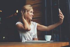 Jeune jolie femme avec le beau sourire posant tout en se photographiant sur l'appareil-photo de téléphone portable Photos libres de droits