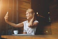 Jeune jolie femme avec le beau sourire posant tout en se photographiant sur l'appareil-photo de téléphone portable Image libre de droits