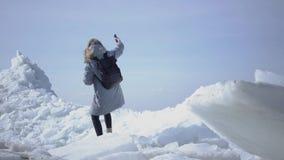 Jeune jolie femme blonde dans la veste chaude marchant sur le glacier avec la carte dans des mains, tenant son téléphone portable banque de vidéos