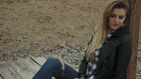 Jeune jolie femme blonde s'asseyant sur le pilier en bois et le repos banque de vidéos
