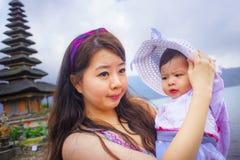 Jeune jolie femme chinoise asiatique heureuse en tant que mère affectueuse tenant le bébé adorable de fille pendant la visite d'e photo libre de droits