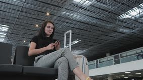 Jeune jolie femme d'affaires Using Smartphone à l'aéroport tout en attendant sa file d'attente l'enregistrement, concept de dépla Photos libres de droits