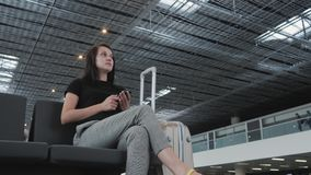 Jeune jolie femme d'affaires Using Smartphone à l'aéroport tout en attendant sa file d'attente l'enregistrement, concept de dépla Images stock
