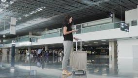 Jeune jolie femme d'affaires Using Smartphone à l'aéroport tout en attendant sa file d'attente l'enregistrement, concept de dépla Photographie stock