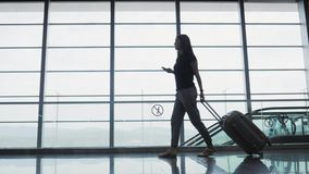 Jeune jolie femme d'affaires Using Smartphone à l'aéroport tout en attendant sa file d'attente l'enregistrement, concept de dépla Photos stock