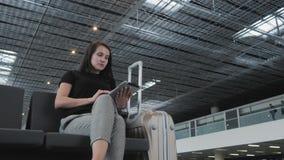 Jeune jolie femme d'affaires Using une tablette à l'aéroport tout en attendant sa file d'attente l'enregistrement, concept de dép Images libres de droits
