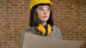 Jeune jolie femme d'architecte prévoyant le nouveau projet, le regard en avant, le sourire et l'inclination de tête, sûre, fond d banque de vidéos