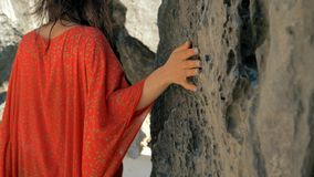 Jeune jolie femme dans des doigts de découverte de robe rouge au-dessus de pierre sur la plage le jour ensoleillé Femme glissant  banque de vidéos