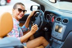 Jeune jolie femme dans des lunettes de soleil se reposant dans des WI d'une voiture de convertible Images stock