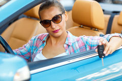 Jeune jolie femme dans des lunettes de soleil se reposant dans des WI d'une voiture de convertible Image stock