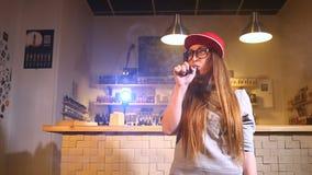 Jeune jolie femme dans la fumée rouge de chapeau une cigarette électronique à la boutique de vape closeup banque de vidéos