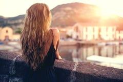 Jeune jolie femme dans la robe noire, au coucher du soleil sardinia l'Italie Image libre de droits