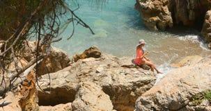 Jeune jolie femme dans le maillot de bain et façade se reposant sur les roches près de la mer clips vidéos