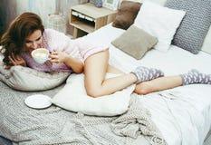 Jeune jolie femme de brune dans sa chambre à coucher s'étendant sur le lit avec la Co photographie stock libre de droits
