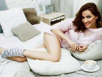 Jeune jolie femme de brune dans sa chambre à coucher se reposant à la fenêtre Li image libre de droits