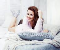 Jeune jolie femme de brune dans sa chambre à coucher se reposant à la fenêtre Li image stock