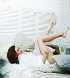 Jeune jolie femme de brune dans sa chambre à coucher se reposant à la fenêtre Li photo stock