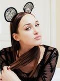 Jeune jolie femme de brune utilisant les oreilles de souris sexy de dentelle, étendant rêver de attente dans le lit Image stock