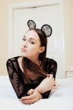 Jeune jolie femme de brune utilisant les oreilles de souris sexy de dentelle, étendant rêver de attente dans le lit Images stock