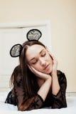 Jeune jolie femme de brune utilisant les oreilles de souris sexy de dentelle, étendant rêver de attente dans le lit Photos stock