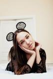 Jeune jolie femme de brune utilisant les oreilles de souris sexy de dentelle, étendant rêver de attente dans le lit Photo libre de droits
