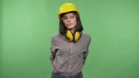 Jeune jolie femme de constructeur se tenant dans les écouteurs, les verres et le casque avec des mains dans des poches et regarda clips vidéos