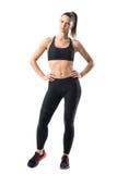 Jeune jolie femme de forme physique dans les guêtres noires et le dessus de réservoir posant avec des mains sur des hanches Images libres de droits