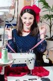 Jeune jolie femme de pin-up drôle dans la robe de point de polka avec la machine à coudre et le portrai de sourire de bande et de  Images stock