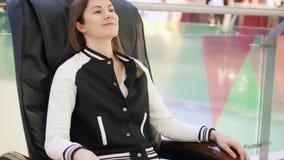 Jeune jolie femme de sourire détendant dans le fauteuil en cuir confortable de massage dans le centre commercial banque de vidéos