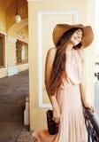 Jeune jolie femme de sourire dans le chapeau avec des sacs sur des achats au devanture de magasin, vrai concept de personnes de m Image libre de droits