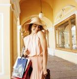 Jeune jolie femme de sourire dans le chapeau avec des sacs sur des achats au devanture de magasin, vrai concept de personnes de m Images stock